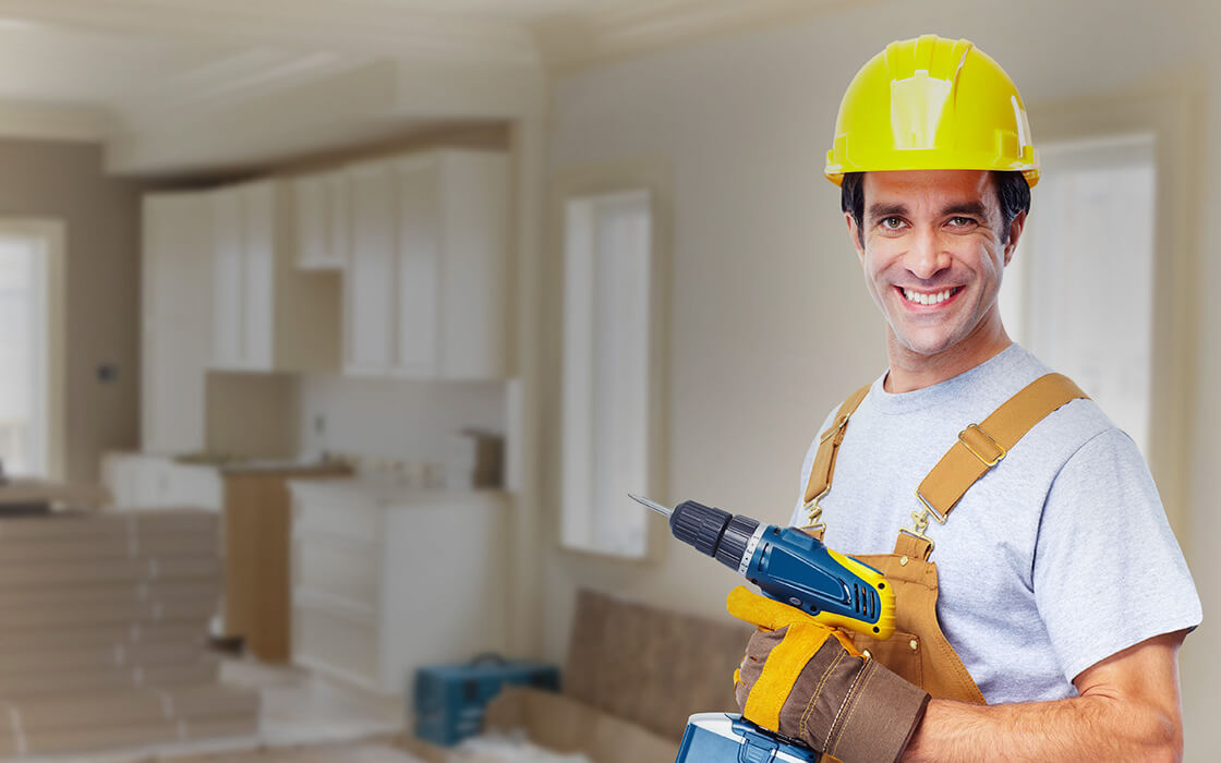 Man in hard hat holding front of frame with a kitchen half built in the backgrounnd